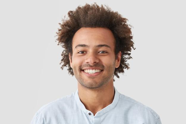 Krullende man met brede glimlach, toont perfecte tanden, wordt geamuseerd door interessante praatjes, heeft borstelig krullend donker haar staat binnen tegen een witte lege muur