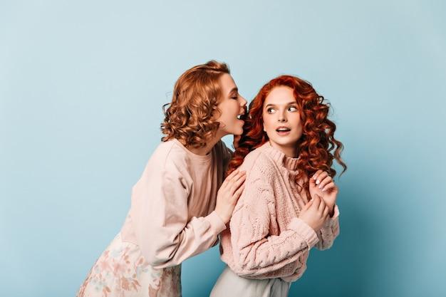 Krullende meisjes praten op blauwe achtergrond. studio shot van vriendinnen in trendy kleding.
