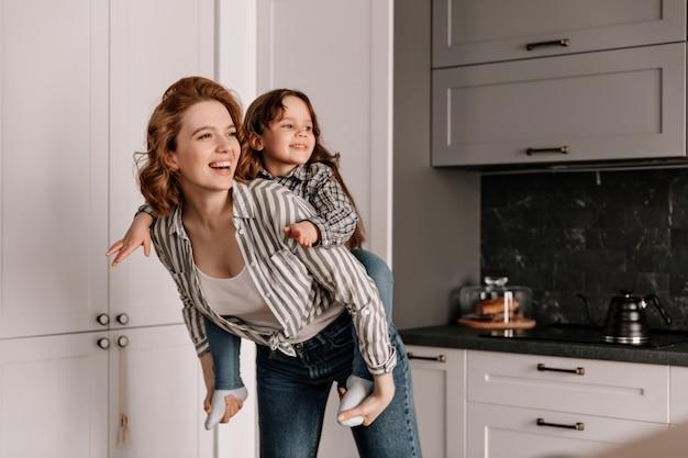Krullende moeder in spijkerbroek speelt met haar dochter in de keuken en lacht.