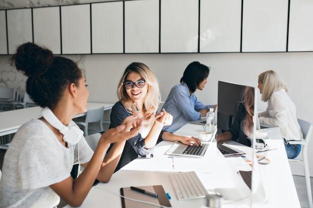 Krullende mulatvrouw in grijs t-shirt legt iets uit aan blonde vriendin. indoor portret van internationale studenten met laptops die zich samen voorbereiden op de test.