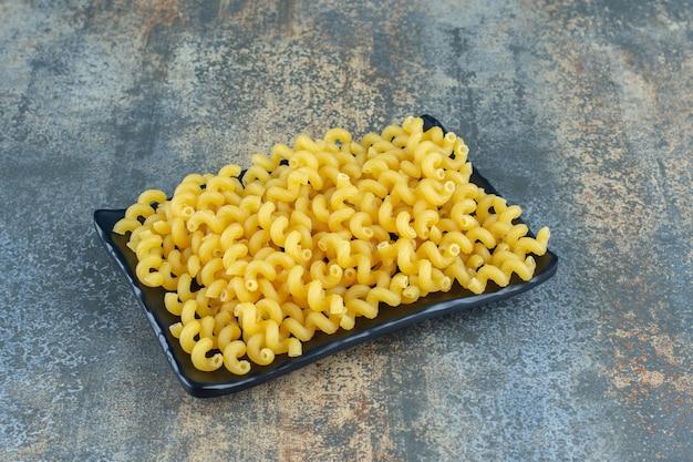 Krullende pasta in de houten plaat, op het marmeren oppervlak.