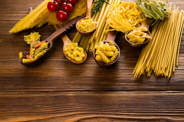 Krullende pasta in lepels op een donkere tafel, verschillende soorten pasta.
