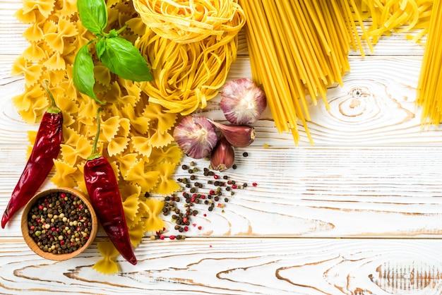 Krullende pasta met peper en basilicum en kruiden op tafel, verschillende soorten pasta, fettuccine, bucatini, spaghetti met gaatjes