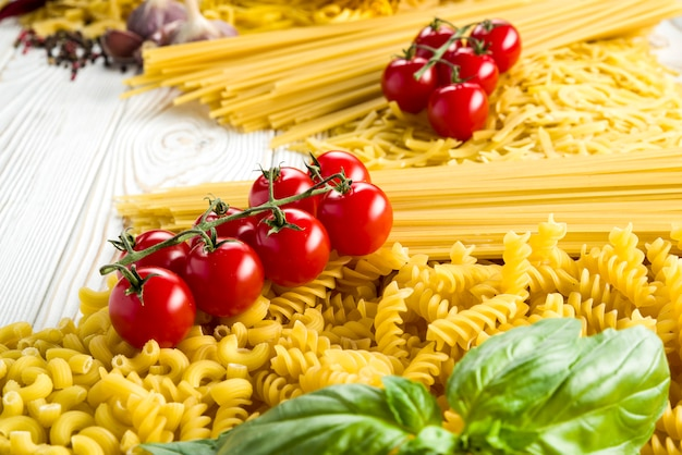 Krullende pasta met peper en basilicum en tomaten en kruiden op tafel, verschillende soorten pasta, fettuccine, bucatini, spaghetti met gaatjes