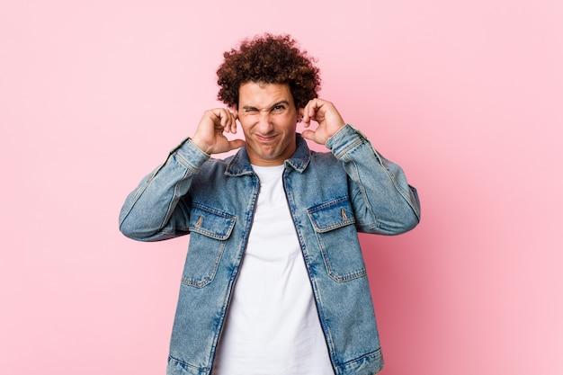 Krullende volwassen man draagt een spijkerjasje tegen roze muur die oren bedekt met handen.