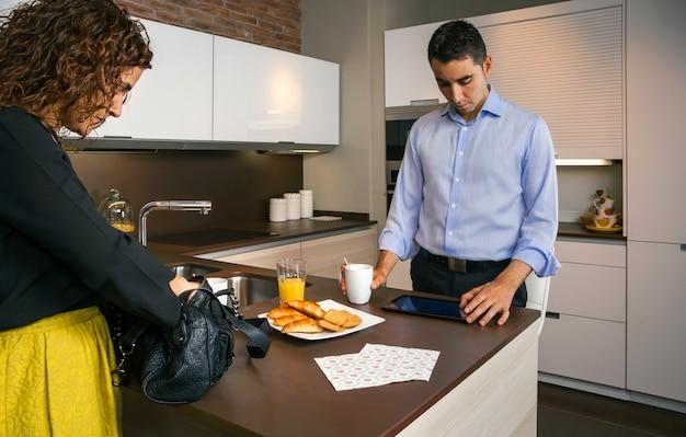 Krullende vrouw bereidt haar tas voor terwijl een jonge man op zoek is naar nieuws in een elektronische tablet en snel ontbijt voordat hij naar zijn werk gaat