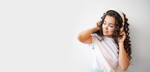 Krullende vrouw die aan muziek met exemplaarruimte luistert