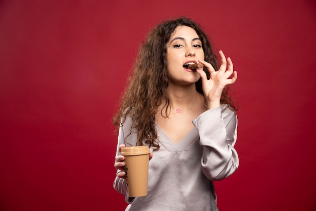 Krullende vrouw die chocolade eet.
