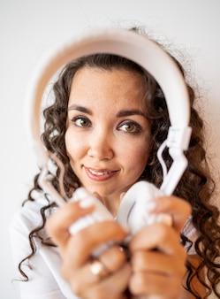 Krullende vrouw die een hoofdtelefoon houdt