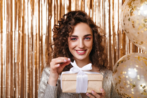 Krullende vrouw die in een goed humeur de doos van de gift op gouden achtergrond houdt