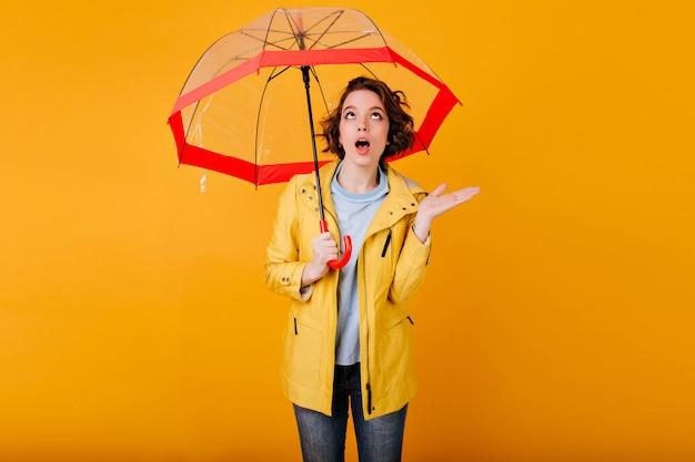Krullende vrouw die in gele jas verbazing uitdrukt die zich onder parasol bevindt. portret van emotionele meisje met paraplu, opzoeken met open mond.