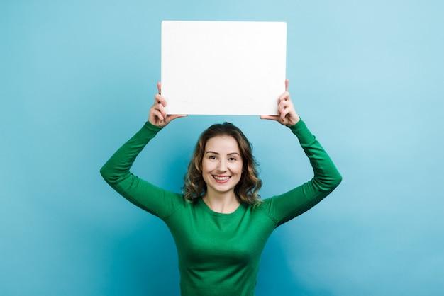 Krullende vrouw die in groene sweater draagt die een ruimte van het witbordexemplaar boven haar hoofd houdt tegen blauwe muur
