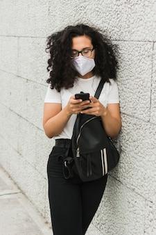 Krullende vrouw die medisch masker buiten draagt