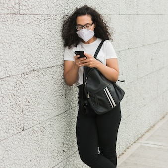 Krullende vrouw die medisch masker draagt