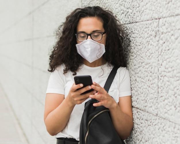 Krullende vrouw die medisch masker in openlucht draagt