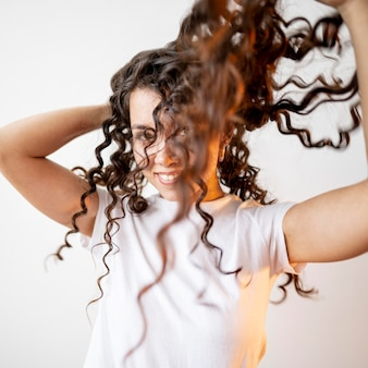 Krullende vrouw die met haar haar speelt
