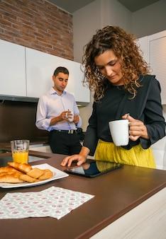 Krullende vrouw die op elektronische tablet kijkt terwijl een jonge man thuis snelle koffie drinkt voordat hij naar zijn werk gaat