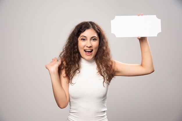 Krullende vrouw die wit papier vasthoudt terwijl ze lacht
