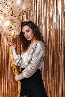 Krullende vrouw in glanzende top met ballonnen op gouden achtergrond