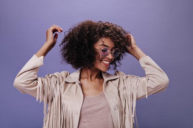 Krullende vrouw in goed humeur dansen op paarse muur