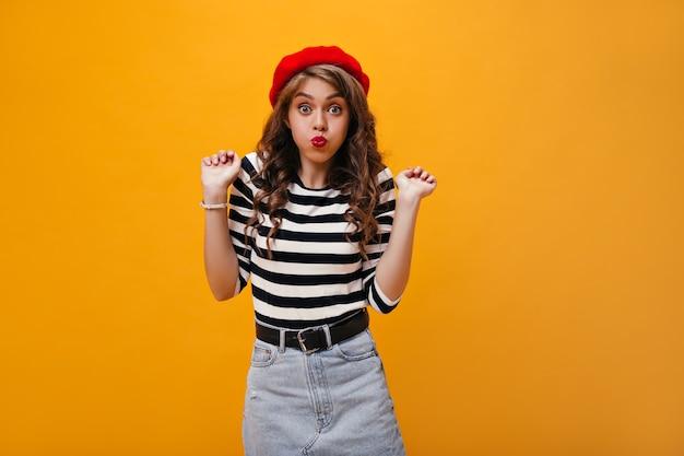 Krullende vrouw in goed humeur maakt grappig gezicht. stijlvol meisje in rode baret en modieuze kleding heeft plezier op geïsoleerde achtergrond.