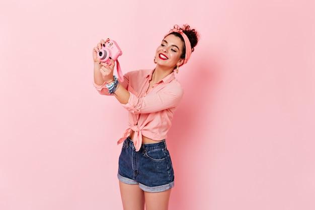Krullende vrouw in hoofdband, roze blouse en spijkerbroek maakt foto op minicamera op roze ruimte.