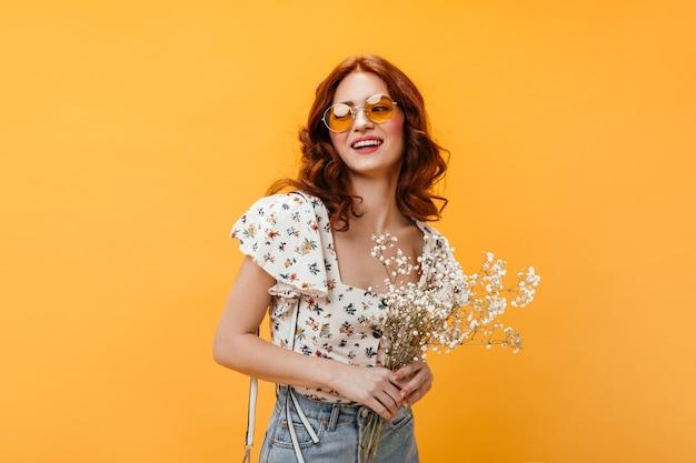 Krullende vrouw in oranje zonnebril lacht zoet en houdt wilde bloemen op oranje achtergrond.