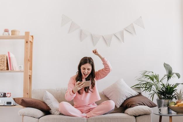 Krullende vrouw in roze pak verheugt zich in het winnen van spel op smartphone