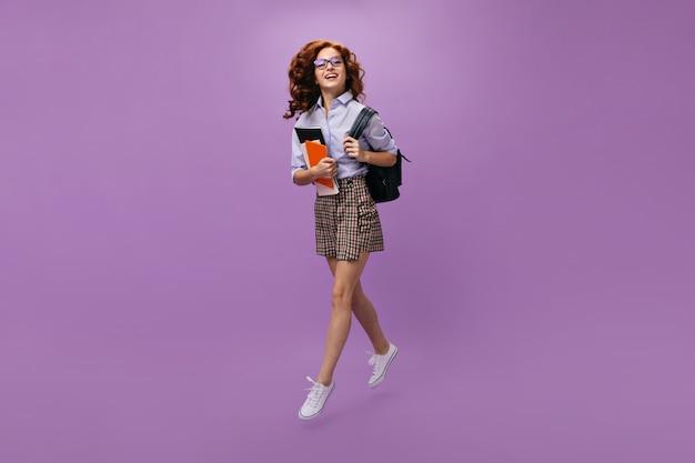 Krullende vrouw in shirt en rok houdt rugzak en notitieboekjes vast
