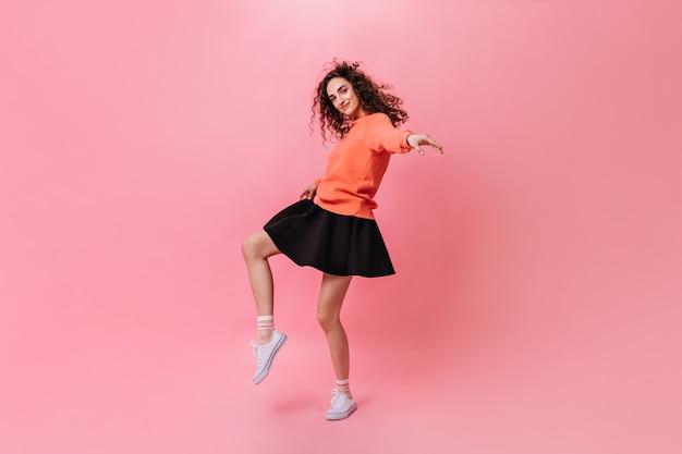 Krullende vrouw in stijlvolle outfit dansen op roze achtergrond