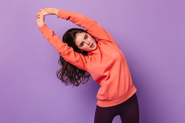 Krullende vrouw in sweatshirt kijkt naar voren en sport oefeningen