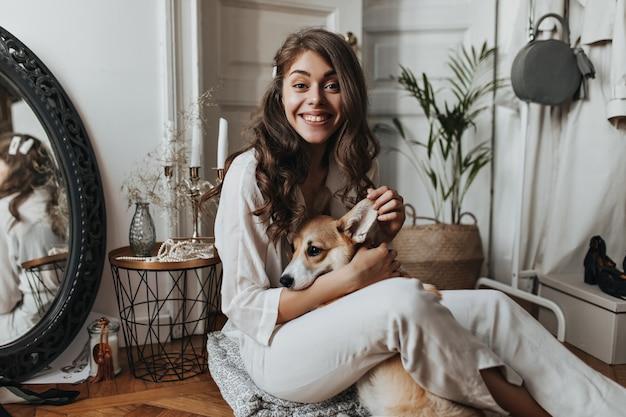 Krullende vrouw in wit overhemd die plezier heeft met hond