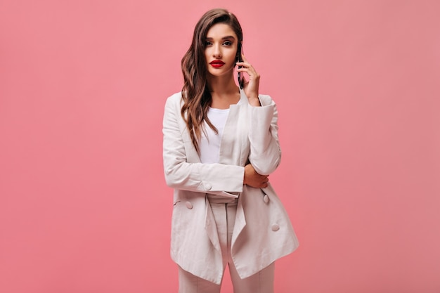 Krullende vrouw in wit pak praat over de telefoon. stijlvolle dame met rode lippen in lichte modieuze outfit op roze geïsoleerde achtergrond.