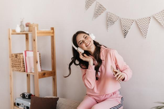Krullende vrouw in witte koptelefoon kijkt naar de voorkant met een glimlach, houdt telefoon vast en geniet van muziek