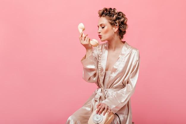 Krullende vrouw in zijden huiskostuum zit op stoel op roze muur en kust telefoon