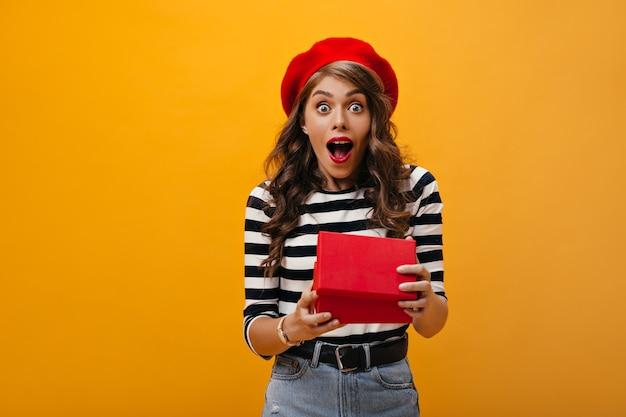 Krullende vrouw kijkt geschokt na het openen van de geschenkdoos. verrast meisje in rode baret en gestreepte blouse op zoek naar camera verheugt zich aanwezig.