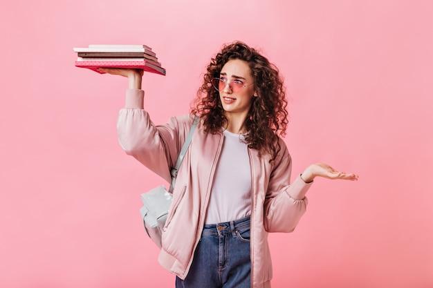 Krullende vrouw kijkt naar boeken en poseren op roze achtergrond