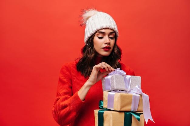 Krullende vrouw met heldere lippen die de strik op de geschenkdoos losmaakt