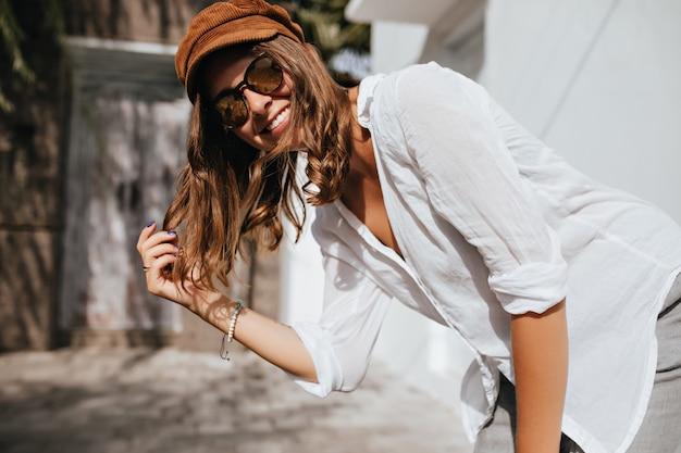 Krullende vrouw met mooie tatoeage op haar arm lacht. vriendelijk meisje in wit overhemd en pet kijkt naar de camera op de ruimte van gezellige huizen.