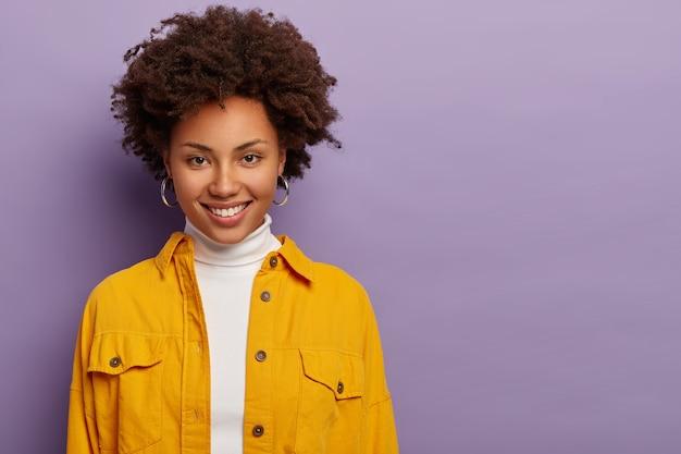 Krullende vrouw met zachte glimlach, tedere blik, praat over aangenaam onderwerp, draagt oorbellen en stijlvolle gele jas, geïsoleerd op paarse achtergrond