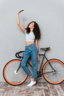Krullende vrouw selfie maken op smartphone met fiets