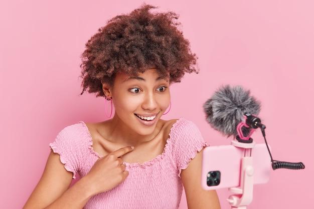 Krullende vrouwelijke vlogger registreert thuis uitgezonden punten naar zichzelf en vraagt met wie ik online chat met abonnees streamt live video lacht positief in de camera geïsoleerd over roze
