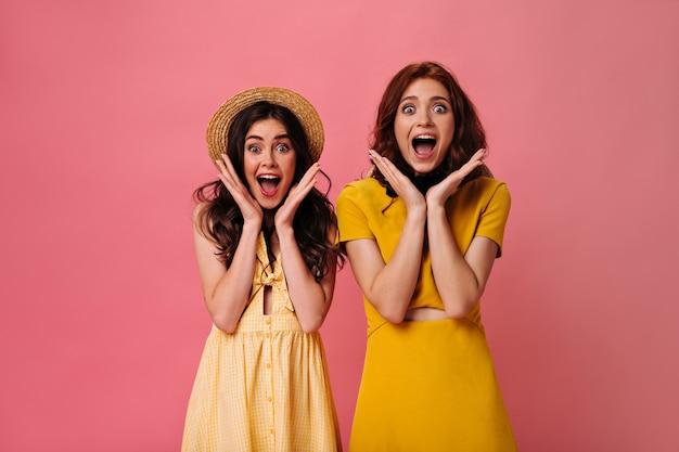 Krullende vrouwen kijken verrassend in de camera op roze muur