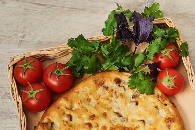 Kubdari is een traditioneel georgisch gerecht van met vlees gevuld geurig brood, met name een nationaal gerecht van de svans op een houten tafel