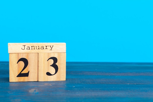 Kubus houten blok met alfabet dat het woord 23 januari bouwt