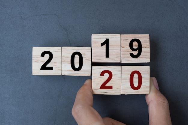 Kubus met flip-overblok 2019 tot 2020 woord op tabelachtergrond