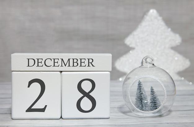 Kubus met tekst van cijfers en een maand, 28 december, het einde van het jaar en samengevat.