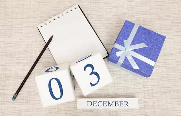 Kubuskalender voor 3 december en geschenkdoos, in de buurt van een notitieboekje met een potlood