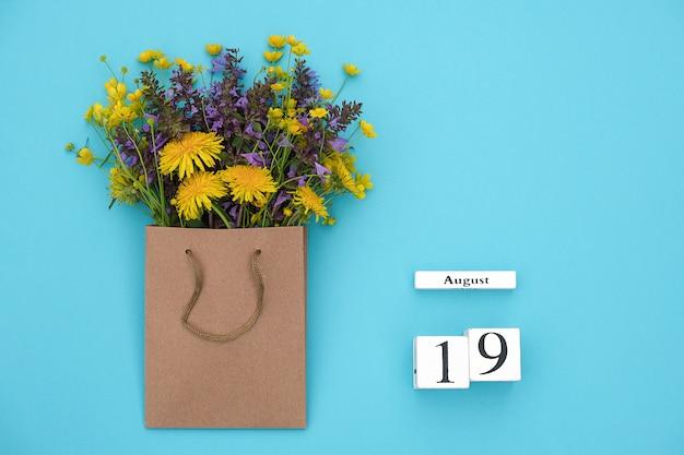 Kubussen kalender 19 augustus en veld kleurrijke rustieke bloemen in ambachtelijke pakket op blauwe achtergrond