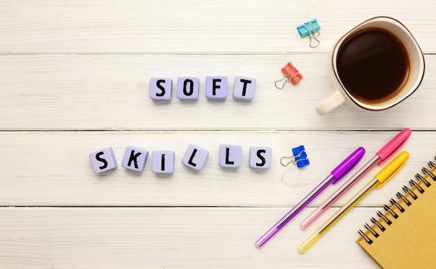 Kubussen met de afkorting soft slills,, koffie en kantoorbenodigdheden op een witte achtergrond